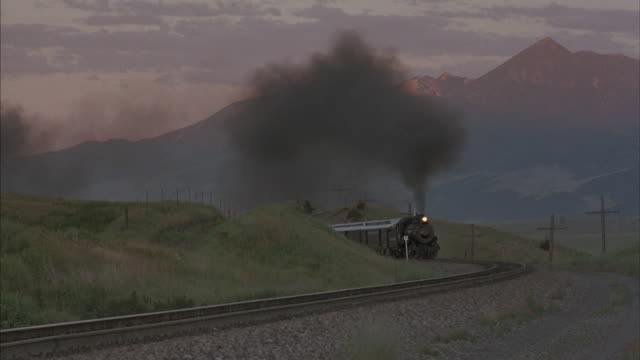 Medium shot of a steam train approaching around a bend.