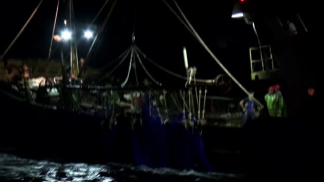 Medium shot of a suspicious boat dropping a blue fishing net into the water zooming in on the fishing net within the area of Japanese waters where...