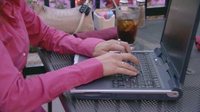 medium shot of a teen girl working on a lap top computer at an outdoor cafe - 2004 stock-videos und b-roll-filmmaterial