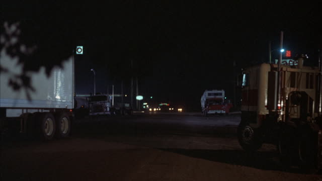 medium shot of a texaco truck-stop with semi-trucks and cars moving through and parking. - 大型トレーラー点の映像素材/bロール