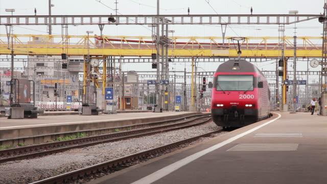 medium shot of a train approahing at the zurich train station - eisenbahn stock-videos und b-roll-filmmaterial
