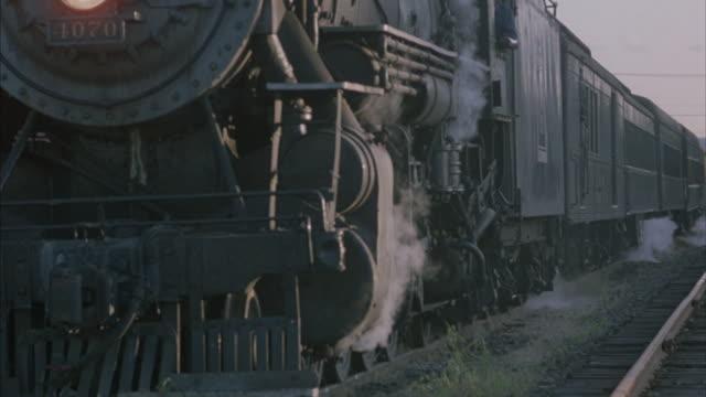medium shot of a train engine starting to move. - zug mit dampflokomotive stock-videos und b-roll-filmmaterial