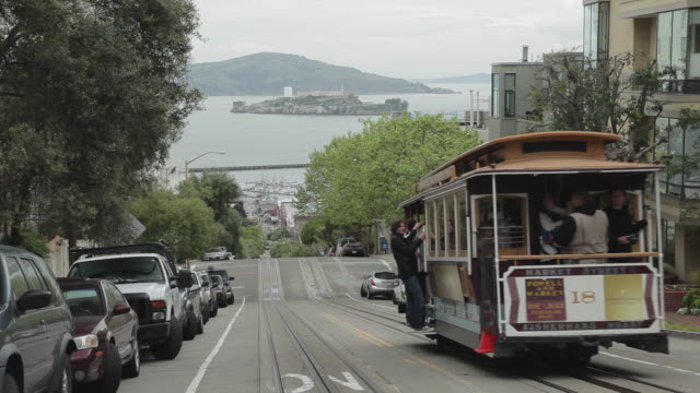 Medium Shot of a trolley passing in San Francisco with Alctraz in the background