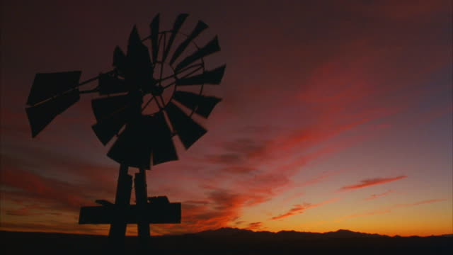 medium shot of a turning windmill in silhouette against a beautiful pink and orange sky. - prärie stock-videos und b-roll-filmmaterial