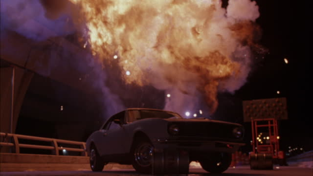 Medium shot of a vintage Ford Mustang exploding.