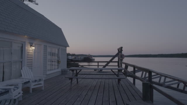 Medium shot of a waterfront house in Boothbay Harbor early in the evening