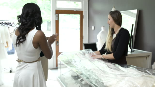 Medium shot of a woman buying a wedding dress