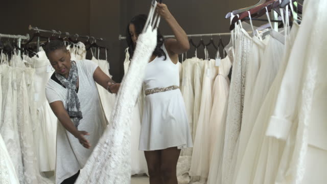medium shot of a woman choosing a wedding dress - wedding dress stock videos and b-roll footage