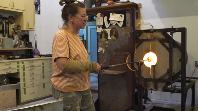 medium shot of a woman heating glass in a furnace - glasbläser stock-videos und b-roll-filmmaterial