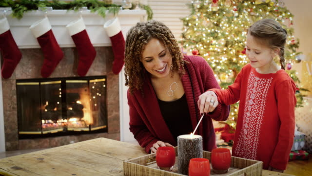 medium shot of a woman lighting candles with her daughter - christmas stocking stock videos and b-roll footage