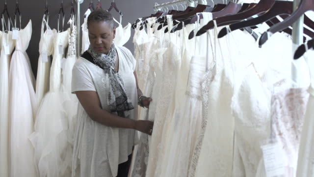 stockvideo's en b-roll-footage met medium shot of a woman looking at wedding dresses - alleen één oudere vrouw