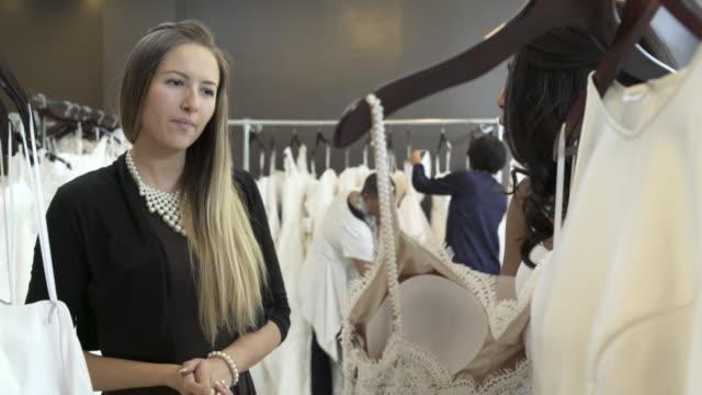 medium shot of a woman looking at wedding dresses - abito da sposa video stock e b–roll