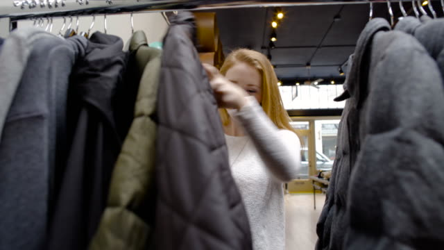 medium shot of a woman picking a coat at a shop - warm clothing stock videos and b-roll footage