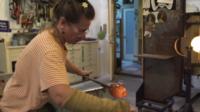 medium shot of a woman shaping glass in a workshop - glasbläser stock-videos und b-roll-filmmaterial