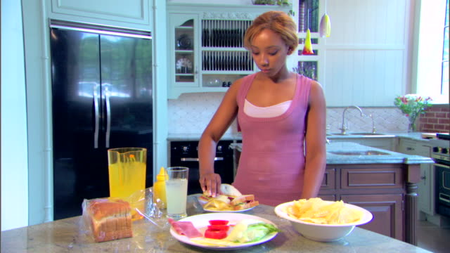 medium shot of a woman standing in her kitchen eating potato chips. - 塩味スナック点の映像素材/bロール