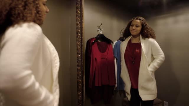 vídeos de stock e filmes b-roll de medium shot of a woman trying on a cardigan - cabine de loja
