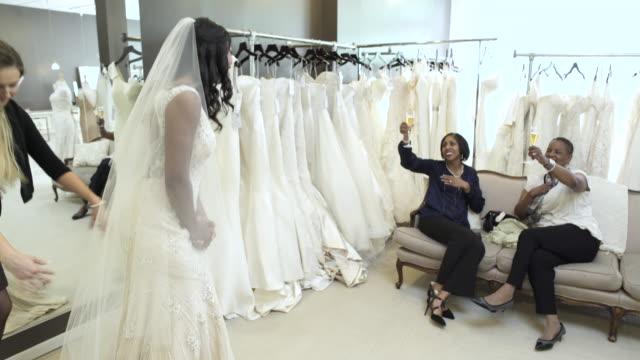 medium shot of a woman trying on a wedding dress - wedding dress stock videos and b-roll footage