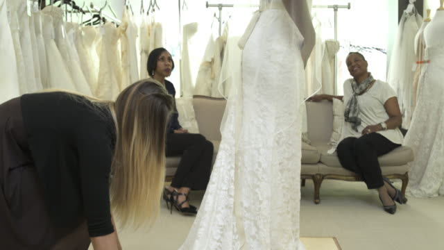 medium shot of a woman trying on a wedding dress - wedding dress stock videos and b-roll footage