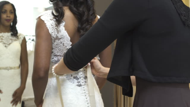 medium shot of a woman trying on a wedding dress - dress stock videos & royalty-free footage