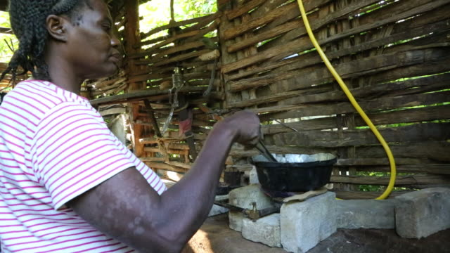 A medium shot of a woman who is cooking up some food in a small pot on a selfmade stove by means of biogas on a plantation near Pilate Haiti