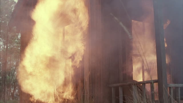 Medium shot of a wood cabin bursting into flames.