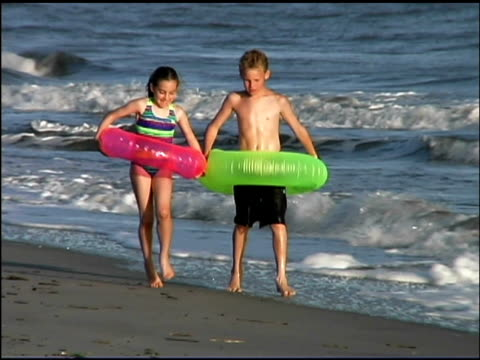 medium shot of a young boy and girl walking together in the ocean surf. both are wearing bathing suits and carrying innertubes. - see other clips from this shoot 1135 stock videos & royalty-free footage