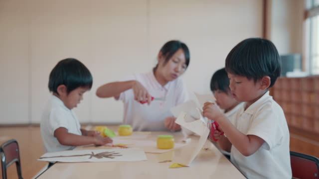 medium shot of a young boy cutting paper in his preschool art class - uniforme scolastica giapponese video stock e b–roll