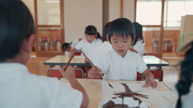 medium shot of a young boy painting a picture in his preschool art class - japanese school uniform stock videos & royalty-free footage