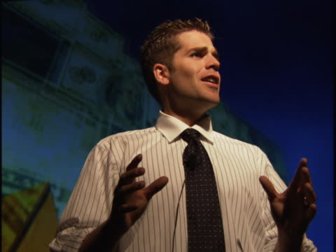 medium shot of a young business man in a shirt and tie as he gives a presentation