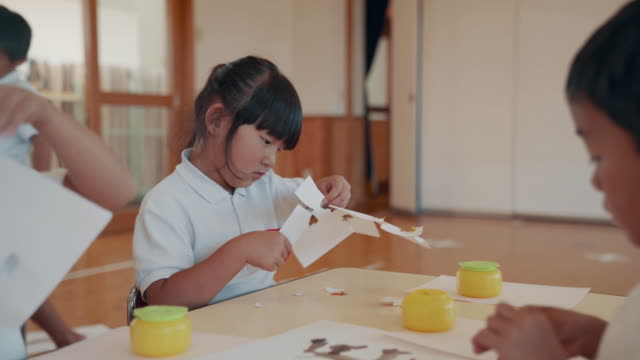 medium shot of a young girl cutting paper in her preschool art class - japanese school uniform stock videos & royalty-free footage