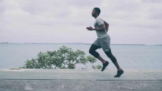 medium shot of a young man jogging along the coast in slow motion - side view stock videos & royalty-free footage