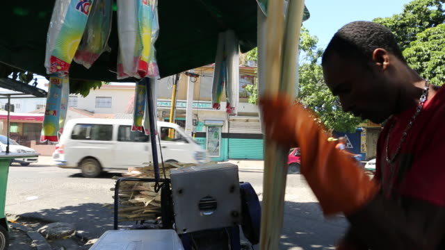 santo domingo dominican republic november 30 2012 a medium shot of a young man who is splitting a sugar cane in two with a knife before he is putting... - insel hispaniola stock-videos und b-roll-filmmaterial