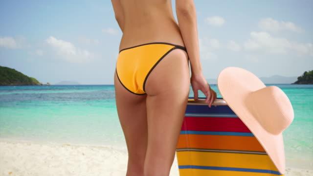 medium shot of a young white girl standing next to her lounge chair in her yellow bikini - white点の映像素材/bロール