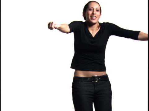 medium shot of a young woman as she dances playfully against a white background - baggy jeans stock videos & royalty-free footage