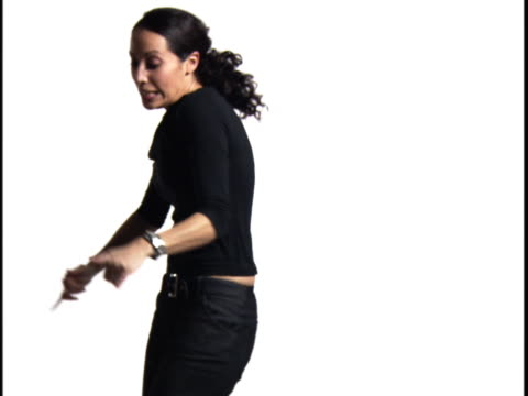 medium shot of a young woman as she shakes and grooves against a white background - baggy jeans stock videos & royalty-free footage