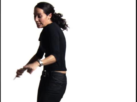 vídeos y material grabado en eventos de stock de medium shot of a young woman as she shakes and grooves against a white background - sólo mujeres jóvenes
