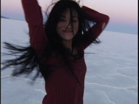 medium shot of a young woman as she turns and smiles playfully in a desert at sunset