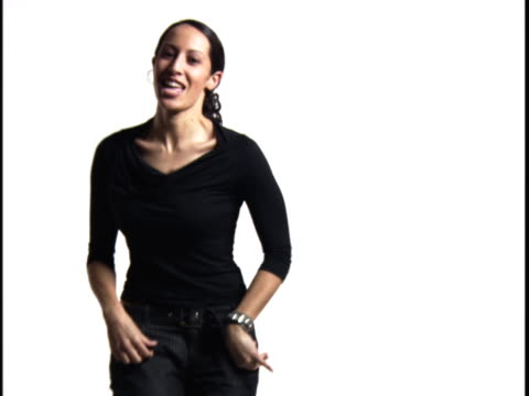 medium shot of a young woman as she turns around dancing against a white background - baggy jeans stock videos and b-roll footage