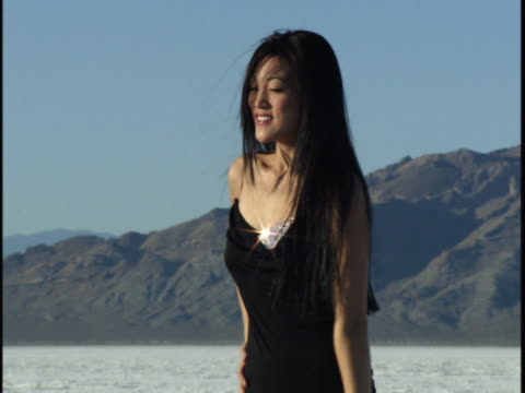 medium shot of a young woman in a black dress as she smiles and poses in a desert