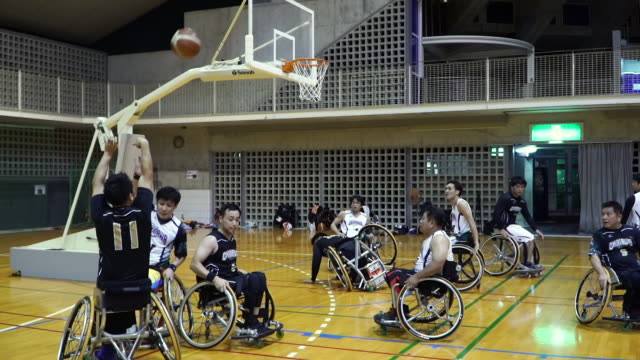 medium shot of adapted athletes playing professional wheelchair basketball - drive ball sports stock videos & royalty-free footage