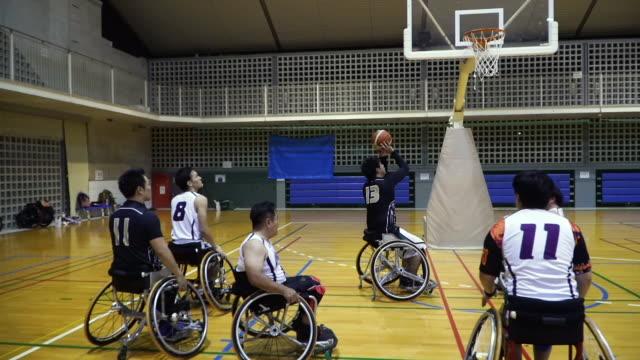 medium shot of adapted athletes playing professional wheelchair basketball - スポーツ バスケットボール点の映像素材/bロール