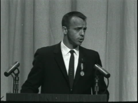 medium shot of alan shepard standing at a lectern with two microphones before him. he is wearing a black suit and tie, and there is a curtain... - alan b. shepard jr stock videos & royalty-free footage