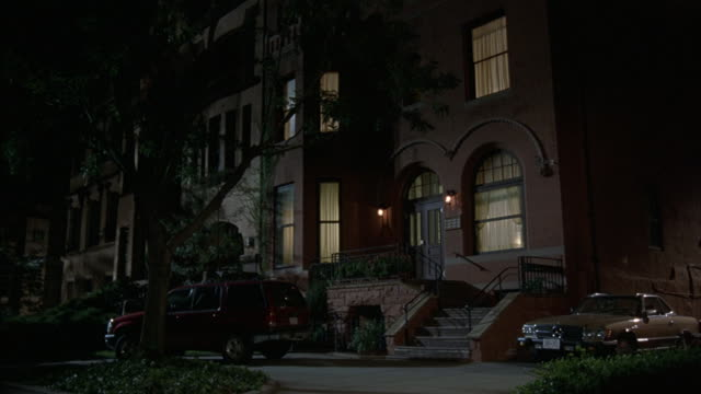A medium shot of an apartment building at night with cars parked out front.