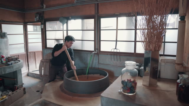 medium shot of an artisan mixing material in a large steaming vat in preparation for making paper by hand - 伝統点の映像素材/bロール