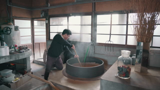 Medium shot of an artisan mixing material in a large steaming vat in preparation for making paper by hand