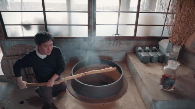 vidéos et rushes de medium shot of an artisan mixing material in a large steaming vat in preparation for making paper by hand - fabrique de papier