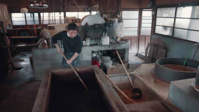 vidéos et rushes de medium shot of an artisan mixing raw material in preparation for making paper by hand - fabrique de papier