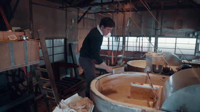vidéos et rushes de medium shot of an artisan preparing materials for making paper by hand - fabrique de papier