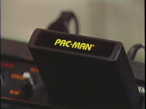 """medium shot of an atari video game console sitting on the glass counter of a video game store. a hand holding a """"pac-man"""" video game cartridge comes... - cartridge stock videos & royalty-free footage"""