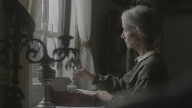 medium shot of an elderly woman writing with a dip pen facing the window - historische szene stock-videos und b-roll-filmmaterial